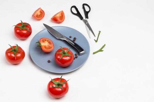 Tomaten und messer auf grauem teller. schere und ganze und geschnittene tomaten auf dem tisch. weißer hintergrund. speicherplatz kopieren. draufsicht