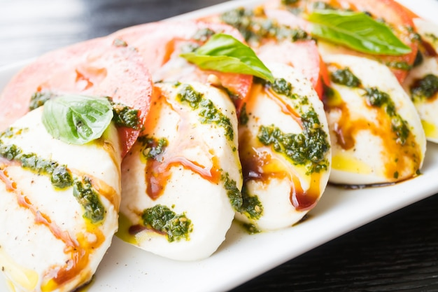 Tomaten- und mozzarellakäsesalat in der weißen platte
