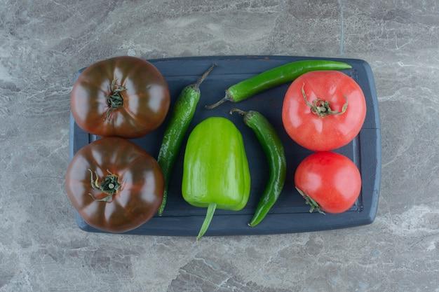 Tomaten und paprika auf dem tablett, auf dem marmortisch.