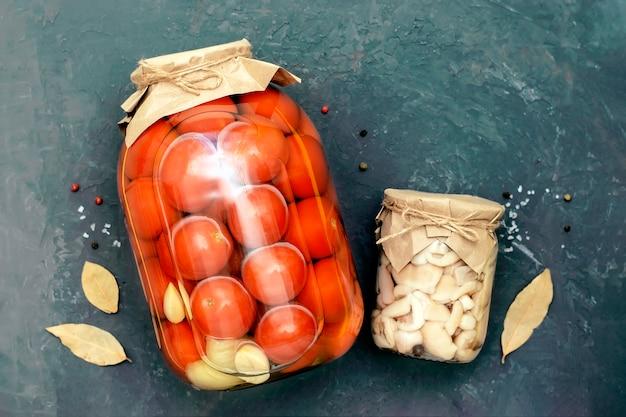 Tomaten und pilze in einem glas auf schwarzem hintergrund, draufsicht. hausgemachte konfitüren.
