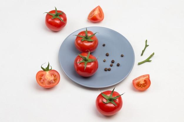 Tomaten und piment auf grauem teller. ganze und geschnittene tomaten auf dem tisch. weißer hintergrund. draufsicht