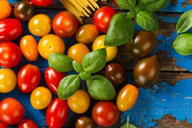 Tomaten verschiedene farben bunt mit basilikum auf hölzernen alten rustikalen hintergrund. draufsicht. horizontal. lebensmittelkonzept