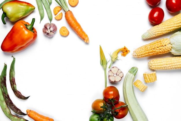 Tomaten, zwiebeln, karotten, knoblauch, rote rüben, pfeffer, mais und grüne bohnen. flache lage, draufsicht, kopienraum