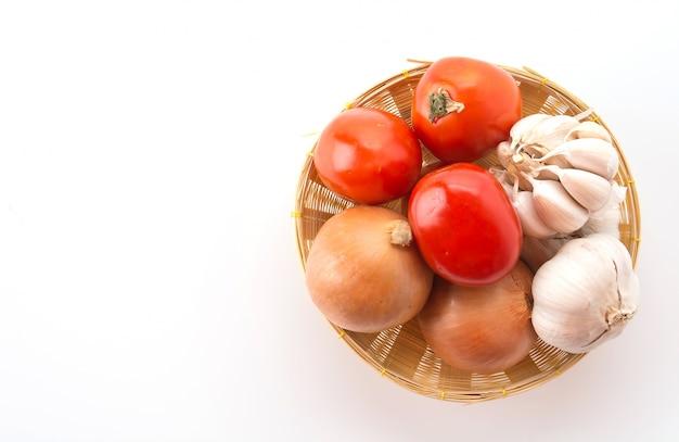 Tomaten, zwiebeln und knoblauch im korb