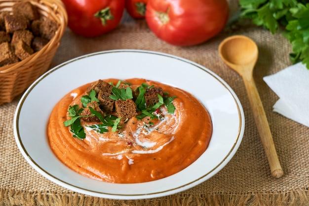 Tomatencremesuppe mit crackern und frischer petersilie