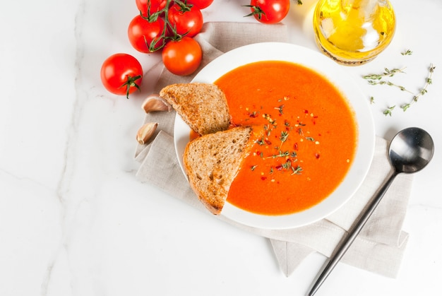 Tomatencremesuppe mit olivenöl und kräutern, mit toastbrot, auf weißem marmor, draufsicht