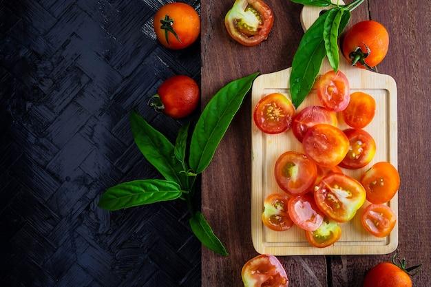 Tomatenhintergrund beinahe eingeschnitten auf einen hölzernen hintergrund