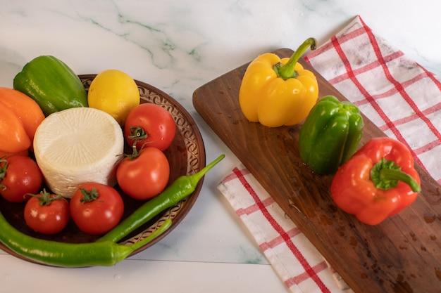 Tomatenkäseplatte mit dreifarbigen paprikaschoten