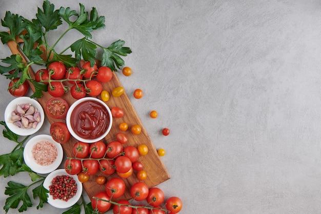 Tomatenketchup-sauce in einer schüssel mit gewürzen, kräutern und kirschtomaten