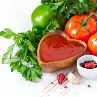 Tomatenketchupsoße in einer hölzernen schüssel und in den bestandteilen