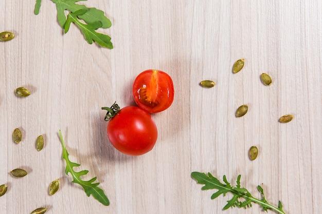 Tomatenkirsche mit arugula und samen auf hellem holztisch. zutaten auf dem tisch