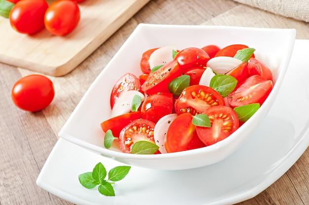 Tomatenkirschsalat mit basilikum, schwarzem pfeffer und zwiebeln