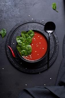 Tomatenpüreesuppe mit spinat in einer schwarzen schüssel, draufsicht