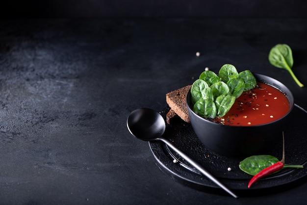 Tomatenpüreesuppe mit spinat in einer schwarzen schüssel, nahaufnahme