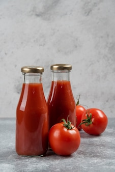 Tomatensaft in gläsern auf marmorhintergrund.