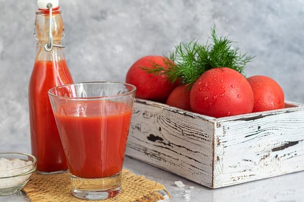 Tomatensaft in glasbechern und frischen tomaten