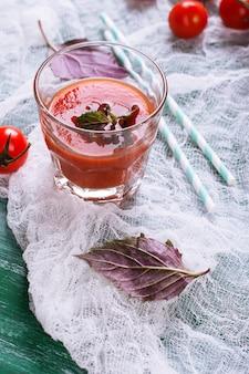 Tomatensaft mit basilikum in einem glas auf hölzernem hintergrund