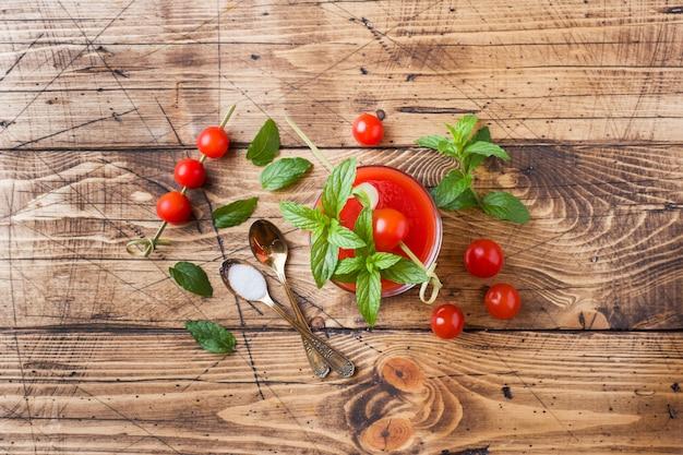 Tomatensaft mit minze im glas und in den frischen tomaten auf einem holztisch. gesunde bio-lebensmittel-konzept.