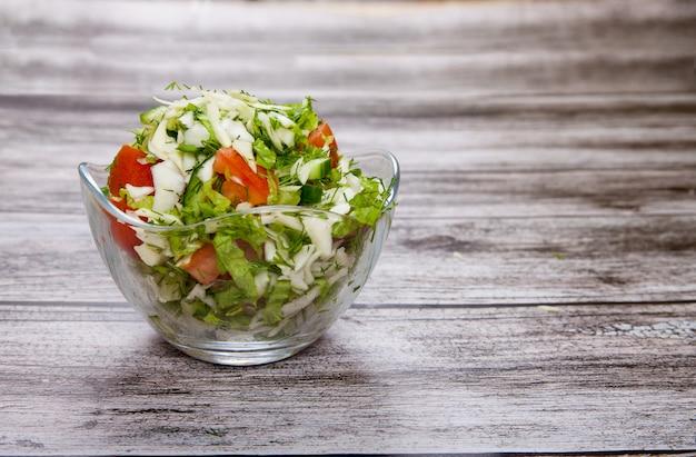 Tomatensalat in einer glasschüssel steht auf einem holztisch