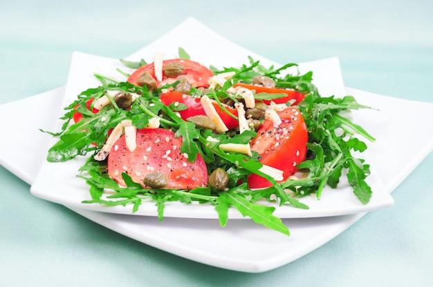 Tomatensalat mit rucolablättern mit käse und sesam