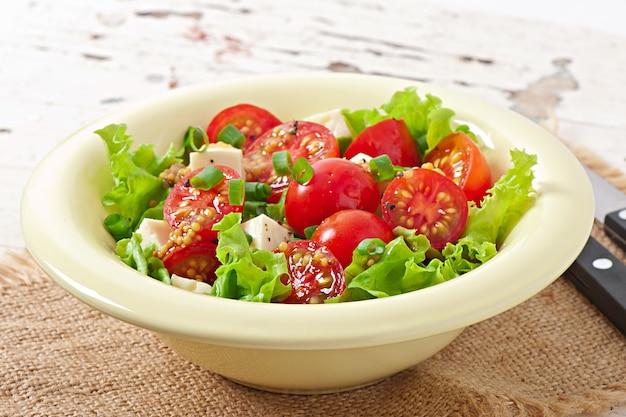 Tomatensalat mit salat, käse und senf-knoblauch-dressing