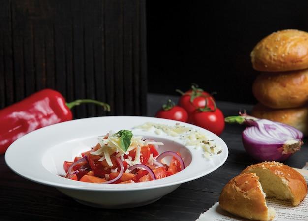 Tomatensalat mit zwiebeln und frisch gehacktem parmesan