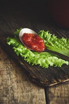 Tomatensauce in einem löffel mit salat