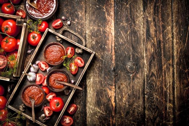 Tomatensauce mit gewürzen und knoblauch im alten tablett auf holztisch.