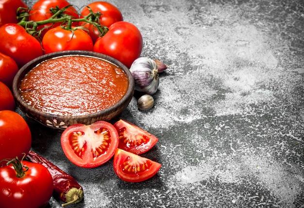 Tomatensauce mit gewürzen und kräutern auf rustikalem tisch.