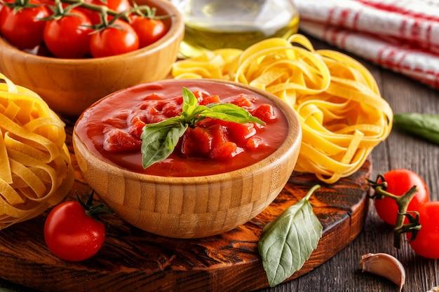Tomatensauce, nudeln, tomaten, knoblauch, olivenöl auf dem alten holz.