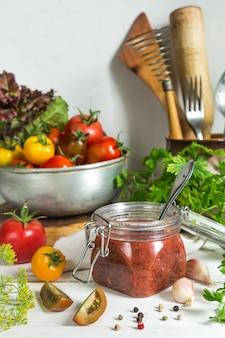 Tomatensauce und frische tomaten, knoblauch, dill, petersilie auf einem hellen hölzernen hintergrund noch