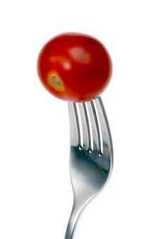 Tomatenscheibe auf gabel aufgespießt
