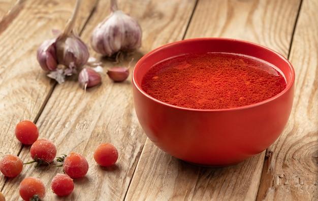 Tomatensuppe auf einem holztisch mit kirschtomaten und knoblauchzehen.