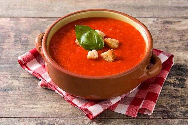 Tomatensuppe in der braunen schüssel auf holztisch
