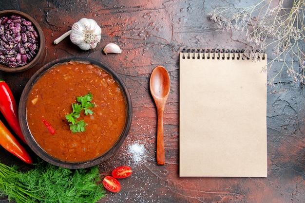 Tomatensuppe in einer braunen schüssel und verschiedenen gewürzen knoblauchzitrone und notizbuch auf gemischter farbtabelle