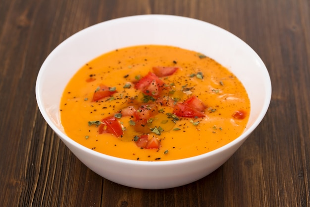 Tomatensuppe in weißer schüssel auf holzoberfläche