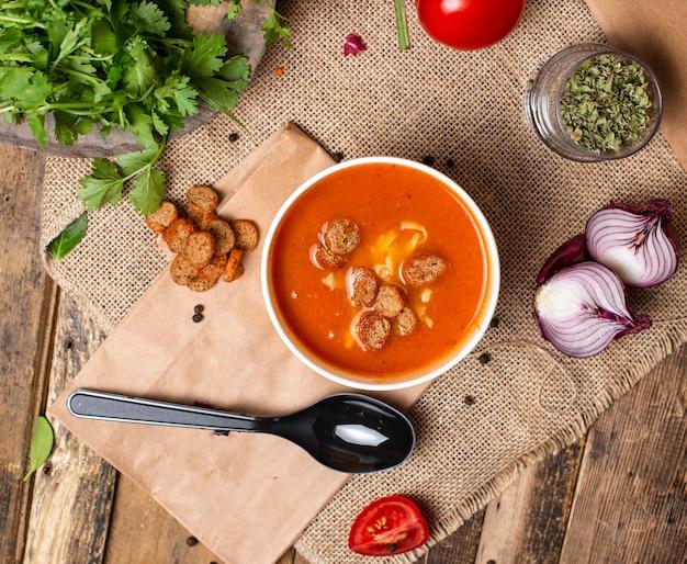 Tomatensuppe mit brotcrackern und käse in der wegwerfschalenschüssel diente mit grünem gemüse.