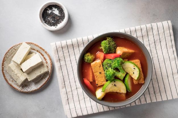 Tomatensuppe mit tofu-käse-brokkoli und zucchini in der draufsicht des veganen lebensmittelkonzepts der schüssel