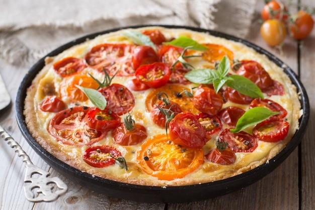 Tomatentarte mit mürbeteig, roten und gelben tomaten, käse und sahne. konzept der gesunden ernährung oder des vegetarischen lebensmittels auf rustikalem hölzernem hintergrund