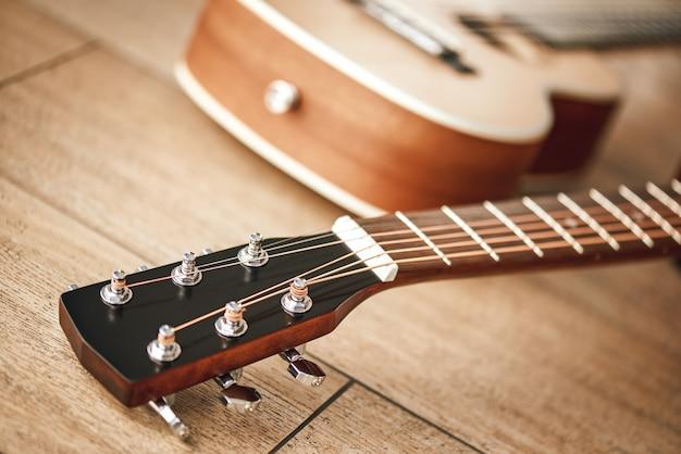 Ton abstimmen. nahaufnahme des gitarrenhalses mit stimmschlüsseln zum einstellen der auf dem holzboden liegenden gitarrensaiten. musikinstrumente. musikanlage. musikgeschäft