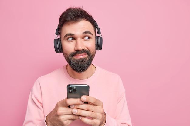Ton an. erfreut, gutaussehender bärtiger mann hört musik über kopfhörer von der playlist, hält das handy, das neue anwendung verwendet, schaut nachdenklich weg