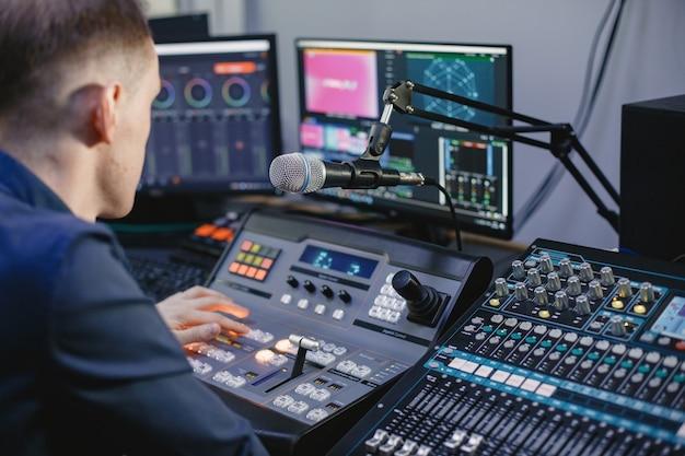 Toningenieur, der im studio mit ausrüstung arbeitet