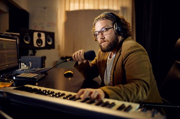 Toningenieur in kopfhörern hält mikrofon, aufnahmestudio-innenraum im hintergrund. synthesizer und audiomischer, musikerarbeitsplatz