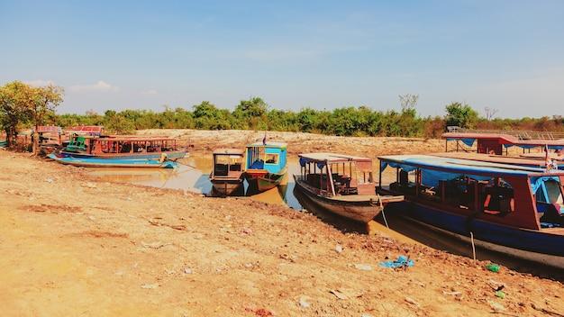 Tonle-sap-see. kampong phluk schwimmendes fischerdorf während der dürrezeit. häuser auf stelzen, menschen und boote. armes land. leben und arbeiten bewohner kambodschas auf dem wasser, in der nähe von siem reap, kambodscha
