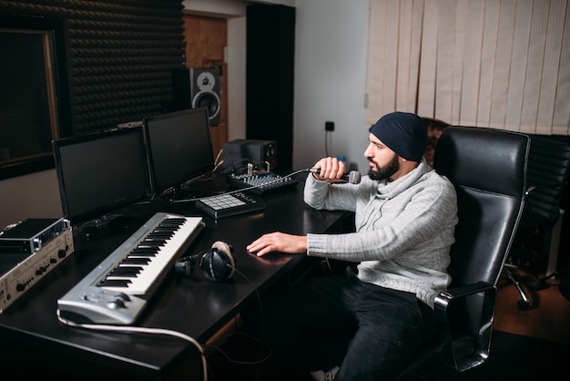 Tonproduzent mit mikrofon im musikstudio. professionelle digitale audioaufzeichnungstechnologie