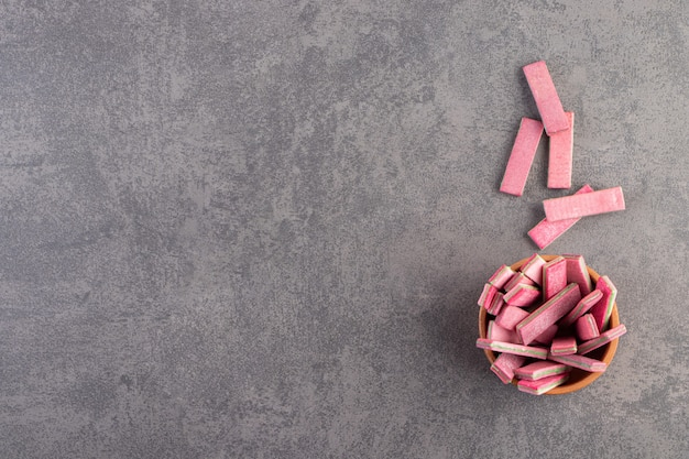 Tonschale der langen rosa kaubonbons auf steintisch.