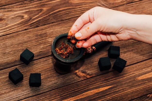 Tonschale für shisha mit kokoskohle, holzmundstücke. mädchen füllt rauchtabak.