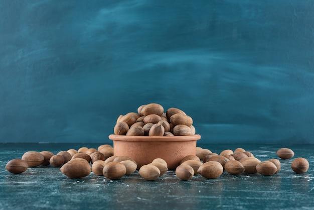 Tonschale mit bio-mandelschalen auf marmortisch.