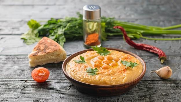 Tonschale mit frischem hummus, einem stück fladenbrot und geschnittenen tomaten auf einem dunklen holztisch
