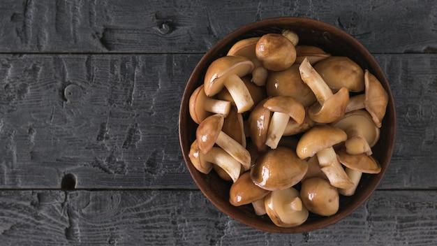 Tonschale mit frischen pilzen aus dem wald auf einem holztisch. natürliche vegetarische küche. der blick von oben.